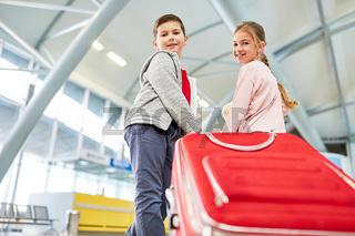 Geschwister im Flughafen Terminal mit Koffer