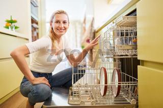 Hausfrau beim Einräumen der Spülmaschine