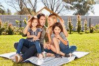 Familie mit zwei Kindern mit Dach über dem Kopf