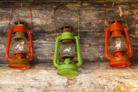 Three colorful lamps or lanterns on log cabin