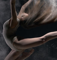 Girl in body jumps in dust cloud black background