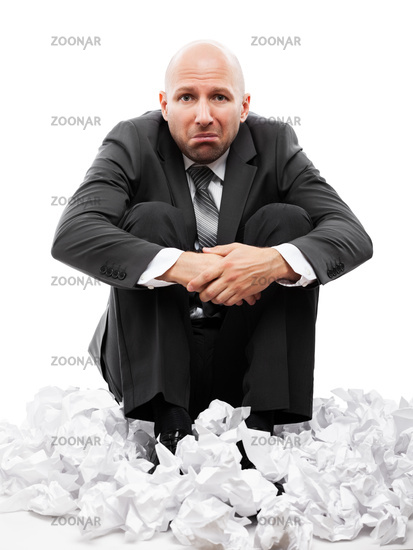Businessman in depression sitting on crumpled torn paper document heap