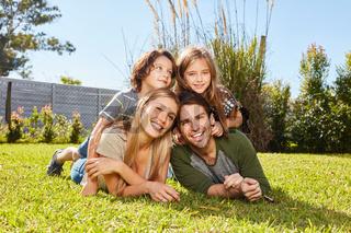 Zwei Kinder liegen mit ihren Eltern auf einer Wiese