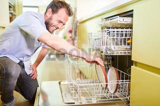 Mann als Hausmann an der Geschirrspülmaschine