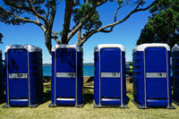 A row of blue toilet cubicles at an outdoor event.