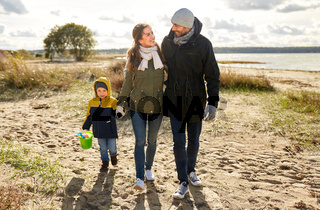 happy family walking along autumn beach