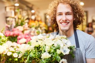 Florist im Blumenladen mit frischen Blumen