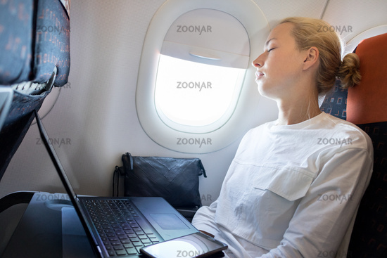 Tired business woman napping on airplane during her business trip woking tasks.