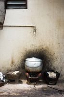 Basic asian cooking stove keeps a metal pot of food hot out the back of a restaurant.