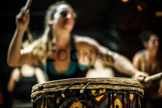 Girl dancing and playing djembe