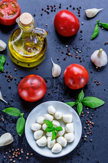Mozzarella, red tomatoes and fresh Basil on a black background. top view. Flat lay. Food concept. Healthy and wholesome food