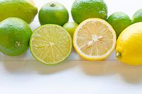 Ripe lemons and limes on white.