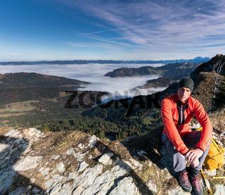 hiker resting on a mountain peak with valleys and forests with cloud banks below him