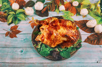 Thanksgiving day dinner table setting with whole roasted chicken on plate
