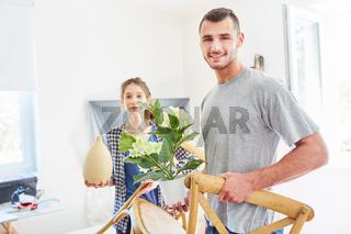 Junges Paar trägt Möbel und Pflanzen beim Umzug
