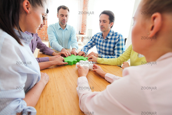 People assembling jigsaw puzzle