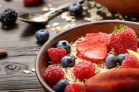 Fruit healthy muesli with peaches strawberry almonds and blackberry in clay dish on wooden kitchen table