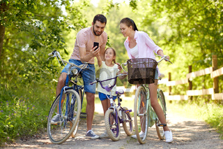 family with smartphone and bicycles in summer park