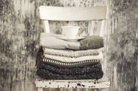 Pile of knitted warm grey and white blankets, scarves and woolen sweaters for winter or fall cold weather on white stool near white and gray wall and coffee on them