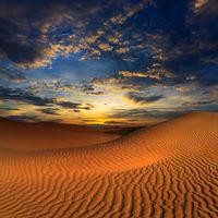 sand dunes in desert at sunset