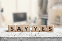 Say yes sign on a wooden desk in a bright room