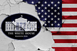 flags of White House Office and USA painted on cracked wall