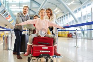 Mädchen breitet die Arme aus und sitzt auf Koffern