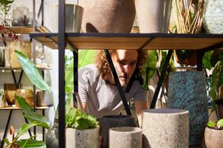 Junger Mann als Florist sortiert Vasen Sortiment