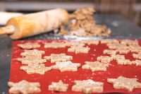 Star shaped cinnamon christmas cookies with dough roll in background