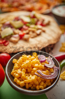 Close up on corn seeds with various freshly made Mexican foods assortment