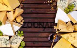Various cheeses on wooden table with empty space.