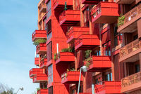 Facade of a modern red apartment house with many balconies seen in Berlin, Germany