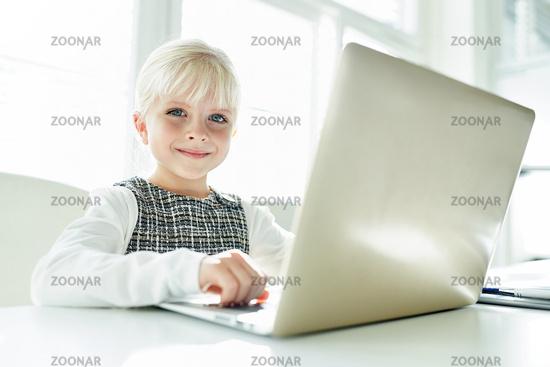 Lächelndes Mädchen als Schreibkraft am Laptop