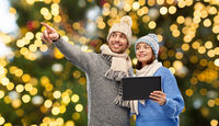 couple with tablet computer over christmas lights