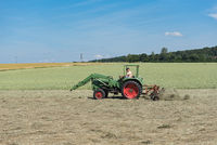 Farmer tractor turns the grass for better drying