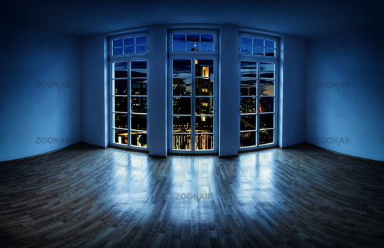 View from an empty apartment to a city at night