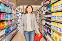 Frau als Kundin beim Einkauf mit Einkaufswagen