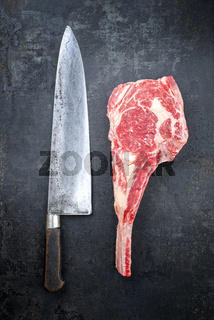 Traditional raw dry aged wagyu tomahawk steak as closeup on an old rustic board with large knife
