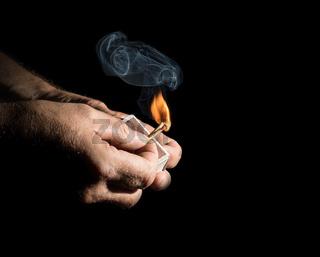 Zwei Hände zünden ein Strichholz an mit kleiner Rauchwolke