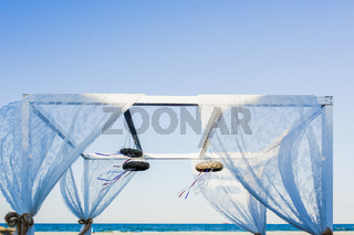 A metal structure decorated for a romantic event, like a wedding on the beach, with blue sky background and sea.