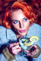 Red-haired woman with a glass of tea in her hand.