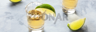 Golden tequila shots with lime slices and salt rims, a panoramic photo