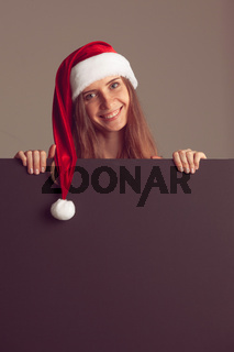 Woman in santa christmas hat holding placard