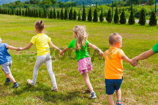 Children holding hands and play on the green lawn