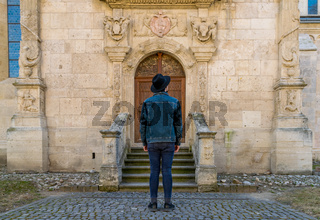 A tourist young man standing against a beautiful old medieval chatedral door. A man  in front of a an old architecture church entrance door in Alba Iulia, Romania