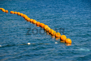 Orange buoys on a rope in the sea. Fencing for swimming in the sea