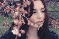 Sad girl hiding in cherry flower branches