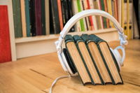 old books with headphones in front of a bookshelf