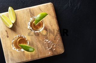 Golden tequila shots with salt and lime slices, overhead shot on black