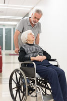 Middle aged man helping and taking to elderly 95 years old woman sitting in the wheelchair.